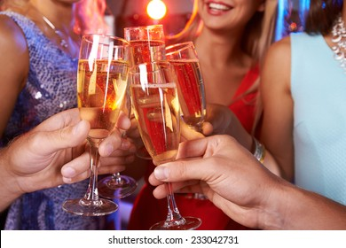 Close-up of hands clinking champagne flutes