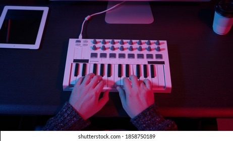 Closeup of hands composing music in night using midi controller. Top view of person playing music with electronic keyboard, midi keys on the table with neon lights
