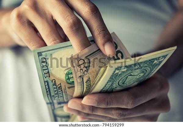 手の接写:金額を数える米ドル、手で金額を数える米ドル、ビンテージトーン効果、収入とビジネスコンセプト。