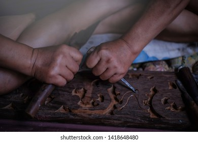Closeup hands of craftsman carve with carve tools in the hands.Traditional craftsman carving wood.Thailand
