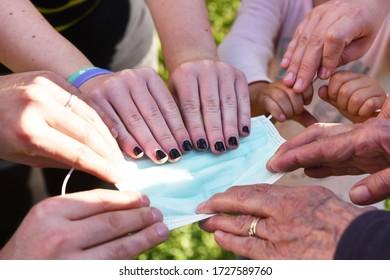 Nahaufnahme von Händen von Menschen unterschiedlichen Alters, die sich einen blauen und weißen Gesichtsmaske schnappen, der den Mangel an medizinischer Versorgung und das Chaos inmitten einer Koronavirus-Pandemie symbolisiert.