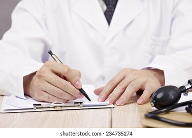 close-up of hands of a doctor writing on notepad.