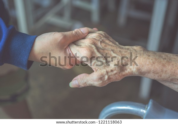 Closeup, Hands of an elderly woman holding the hand of a younger woman. Medical and healthcare concept.