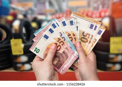 Closeup of hands with euro banknotes in tire shop