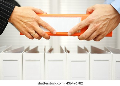 closeup of hands exchanging business documentation