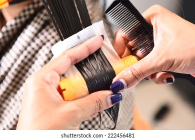 Closeup of the hands of a female hairstylist doing a perm rolling the clients hair onto fine rollers or curlers for a curly or wavy effect