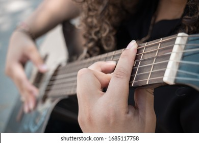 closeup of the hands of a girl playing her acoustic guitar