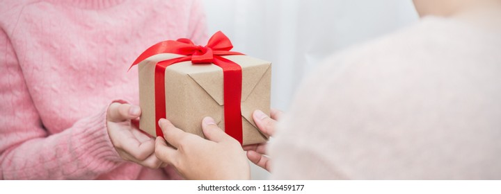 Closeup hands giving surprise gift box, two woman delivery gift brown package box with red ribbon. Boxing day holiday birthday Christmas concept panoramic banner