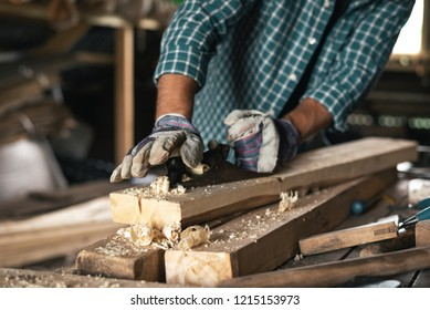 Close-up of the hands of a gloved carpenter with a hand planer handles wood.
