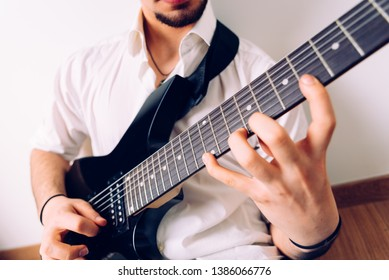 Close-up of the hands of a guitarist performing a song while pressing the strings.
