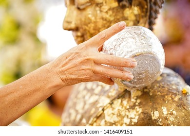 Close-up Hands holding a bowl of water to pour Buddha in the Songkran tradition. Hands of thai people pouring water (bathing) on Buddha Songkran festival. Songkran is new year of Thailand.