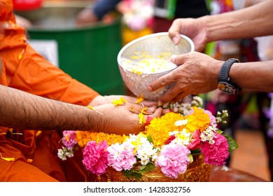 Close-up Hands holding a bowl of water to pour monk in the Songkran tradition. Hands of thai people pouring water (bathing) on Buddha Songkran festival. Songkran is new year of Thailand.