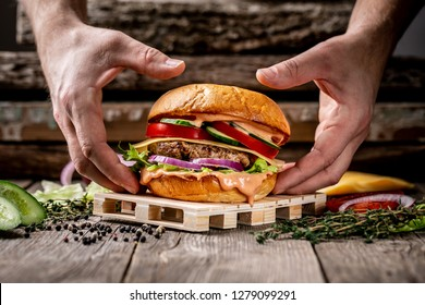 Close-up of the hands holding home made tasty hamburger on wooden vintage table. excess weight set.