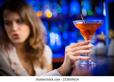 close-up of hands holding the leg of a martini glass with red alcoholic beverage in the background girl