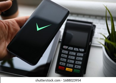 Close-up hands holding smartphone near terminal. Pay for shopping with mobile device, on phone an NFC chip. Ability to pay securely for products and services by contactless payment during quarantine