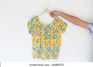 Closeup of Hands holding summer clothes is clothes hanger on white background.