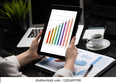 Close-up hands holding tablet on background of financial documents