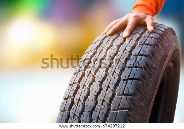 closeup hands holding a tire or tyre on the garage