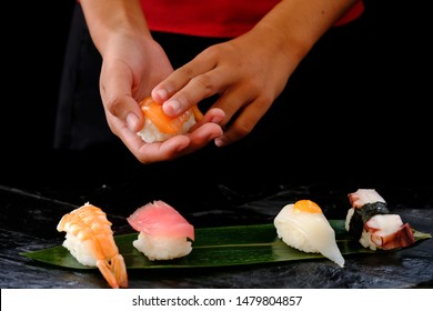 Closeup hands of japanese chef making sushi at restaurant