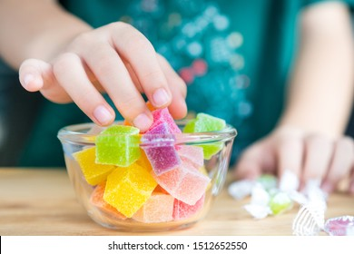 Closeup hands of a little child taking a piece of jelly cube with sugar in a glass bowl. Snacks time, Sugary treats, Party, Kids favorite, Unhealthy, Cavity, Sugar addiction, School, Home, Sweetness