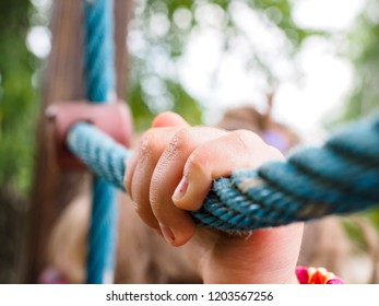 Closeup of hands of little girl climbing on rope web