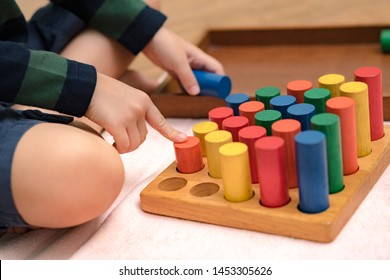 Closeup: Hands of a little Montessori kid (3-6) learning about size, orders, sorting, arranging by engaged colorful wooden sensorial blocks. Educational toys, Cognitive skills, Montessori activity.