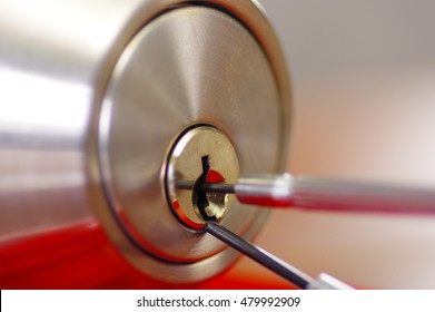 Closeup hands of locksmith using metal pick tools to open locked door