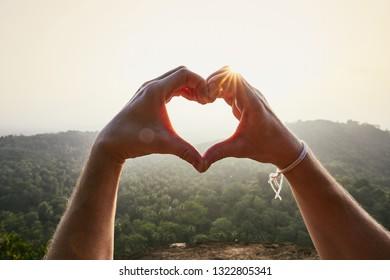 Close-Up of hands making heart shape against landscape at sunset.