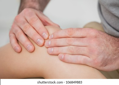 Close-up of hands making a massage on a knee in a room