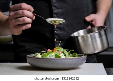Close-up of the hands of a male chef on a black background. Pour sauce from the spoon on the salad dish. Food decoration.