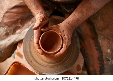 Close-up hands of a male potter in apron making a vase from clay, selective focus