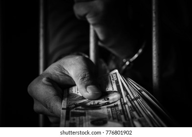 Close-up of hands of male prisoners were shackled by the captors are holding dollars to use as evidence of offences