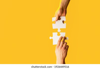 Closeup hands of man connecting jigsaw puzzle. Two hands trying to connect couple puzzle with yellow background. Hand connecting jigsaw puzzle. Man hands connecting couple puzzle piece.