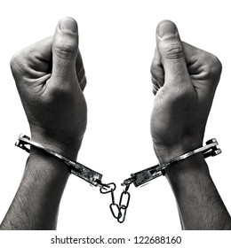 closeup of the hands of a man with handcuffs on a white background