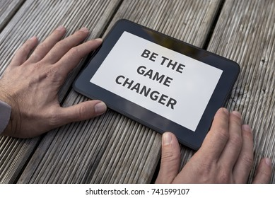 Close-up of the hands of a man holding a PC tablet with a motivational and inspirational message Be the game changer.