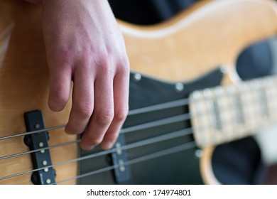 Closeup of hands of a man playing electrical bass guitar,with only his fingers in focus