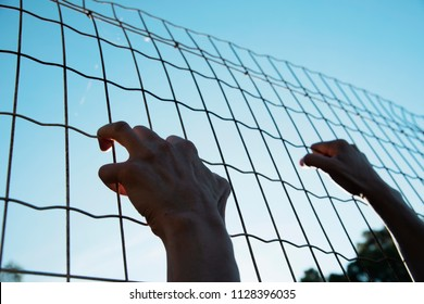 closeup of the hands of a man trying to climb up a metal fence