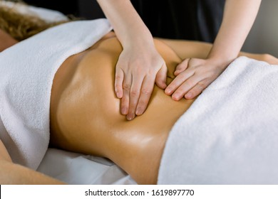Close-up of the hands massaging female abdomen. Therapist applying pressure on belly. Woman receiving massage at medical spa center