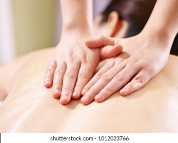 close-up of hands of a masseur massaging back of a young asian woman