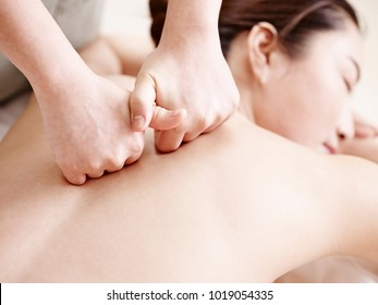 close-up of hands of a masseuse massaging back of a young asian woman.