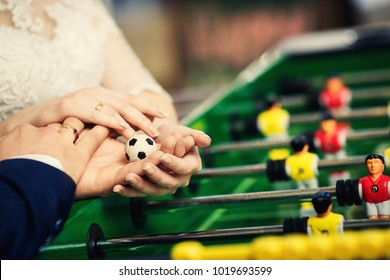 close-up of the hands of the newlyweds holding a football soccer ball over the table football