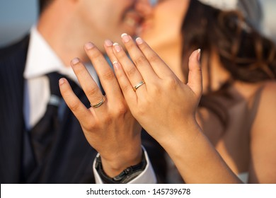 Closeup of hands of newlyweds showing their rings full of joy. People unrecognizable.