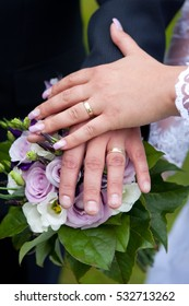 Closeup of hands newlyweds. Hands of the newlyweds with wedding rings on bridal bouquet