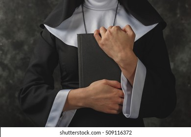 closeup hands of nuns which presses against his chest Bible.Religious nun in religion concept against dark background.