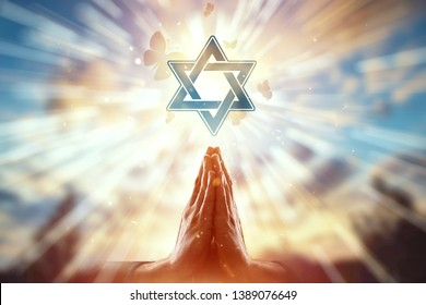 Close-up hands on the background of the symbol of Judaism, prayer, the star of David, a flock of butterflies flies. Judaism, the concept of hope, faith, religion, a symbol of hope and freedom.