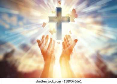 Close-up hands on the background of the symbol of Christian, prayer, catholic cross, a flock of butterflies flies. Christian religion, the concept of hope, faith, religion