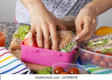 A closeup of hands packing snacks into a pink lunch box