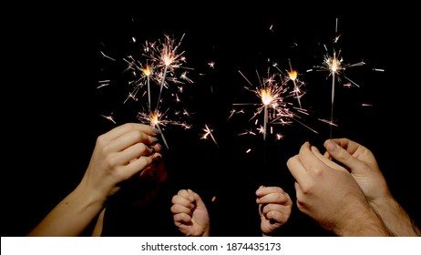 Close-up of hands or palms holding and waving burning sparklers in front of black dark background. Sparkling lights at birthday party, wedding, New Year, Christmas Eve, Xmas. 6k downscale. Bengal fire