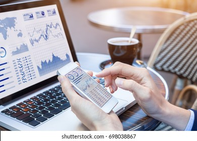 Close-up of hands of person analyzing stock market chart and key performance indicators (KPI) with business intelligence (BI) on notebook computer and smartphone screen, fintech (financial technology)