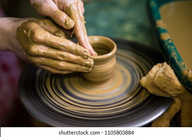 Close-up hands of potter in apron making vase from clay, selective focus. Making it together. Top view of potter teaching to make ceramic pot on pottery wheel